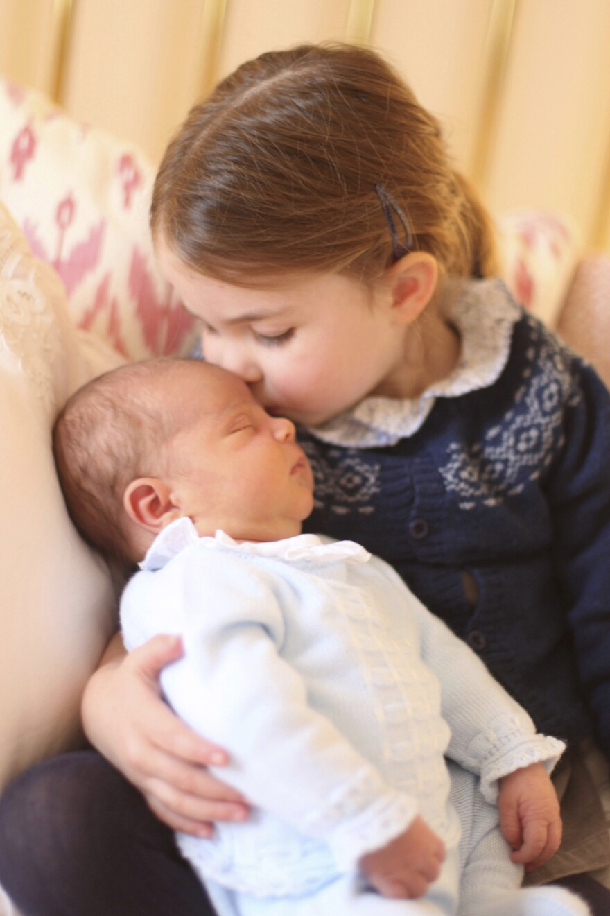 In this May 2, 2018 photograph provided by Kensington Palace, Britain's Princess Charlotte cuddles her brother Prince Louis, on her third birthday, at Kensington Palace, in London.