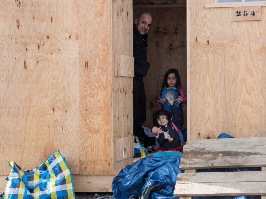 Iraqi Kurds look out from a wooden cabin on March 8, 2016, in Grande-Synthe, northern France, after coming from a nearby site where migrants and refugees have been living in miserable conditions.