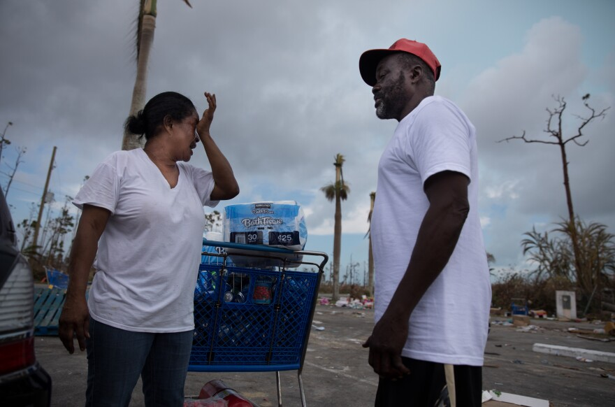 Judy Roker chats with friend John Battles Tate after stocking up on basic provisions, like water, toilet paper and canned goods from Abaco Groceries in Marsh Harbour.