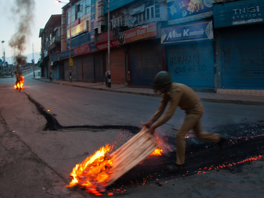 Indian government forces douse a burning tire left by protesters in the Kashmiri city of Srinagar. Violence has swept through the disputed region since separatist rebel Burhan Wani was killed by the Indian army on Friday.