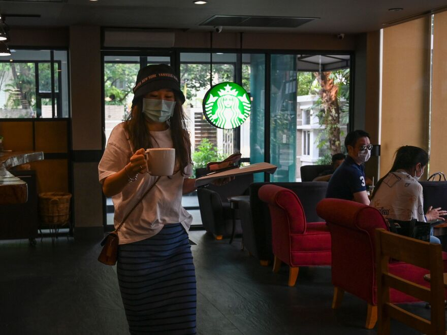 Customers wearing facial coverings at a Starbucks in Bangkok last month. In the U.S., the company is requiring employees to wear coverings starting Tuesday.