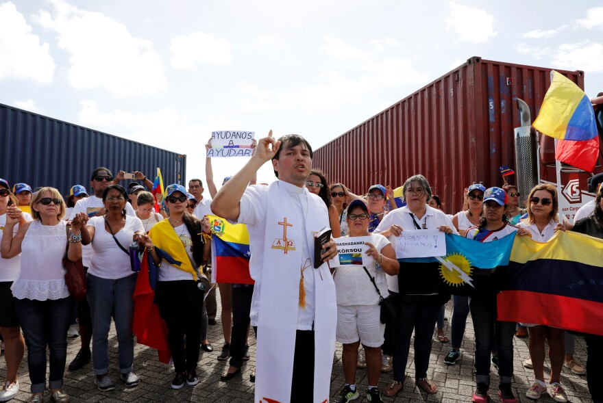 A priest prays with supporters of Venezuela's opposition, who hold Venezuelan flags and signs calling for humanitarian aid, at the port in Willemstad, Curaçao, on Feb. 23.