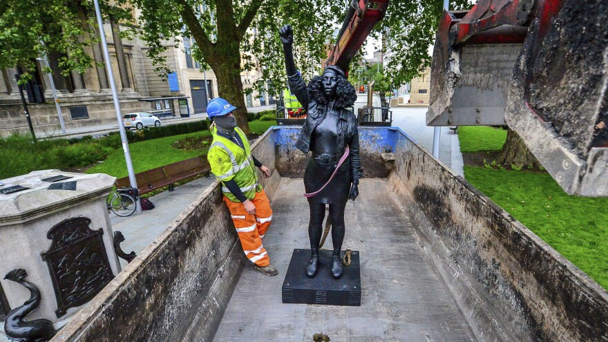 Contractors on Thursday remove Marc Quinn's statue, <em>A Surge of Power (Jen Reid) 2020</em>, after its temporary stint atop the plinth dedicated to slave trader Edward Colston in Bristol. Officials in the British city said the sculpture had been set up without their permission.