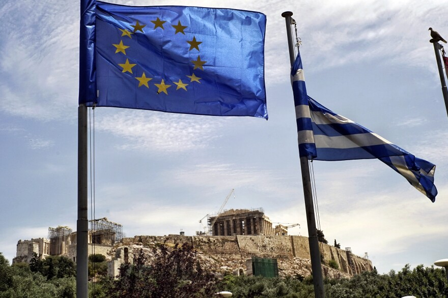 The EU and national flags fly in the foreground of the Parthenon, as Greek voters prepare to decide whether to continue negotiating for more international loans.
