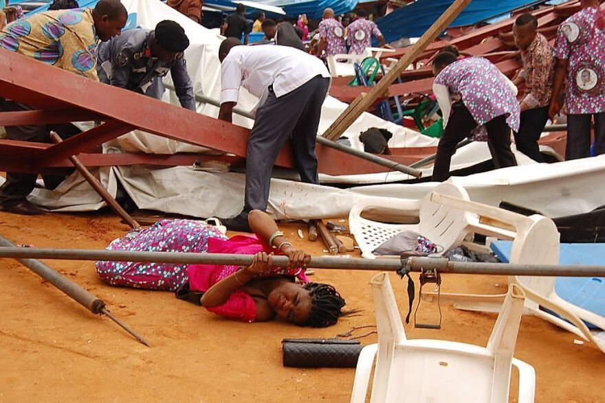 A woman lies under a scaffolding bar Saturday after the collapse at a church in the remote southeastern city of Uyo, the capital of Nigeria's Akwa Ibom state.