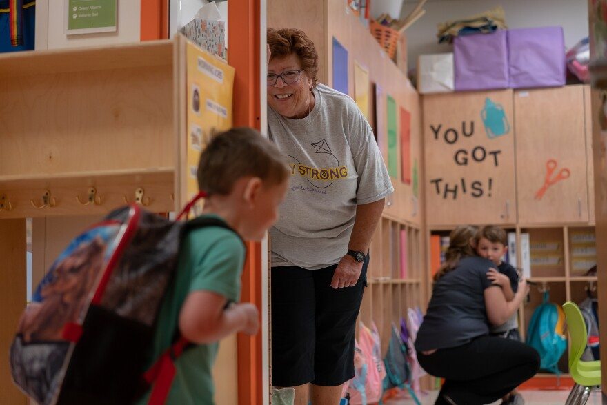 Leslie Forsythe, a substitute teacher at the Affton Early Childhood Center, coaxes a student into a classroom on the first day of school Tuesday, Aug. 13, 2019.