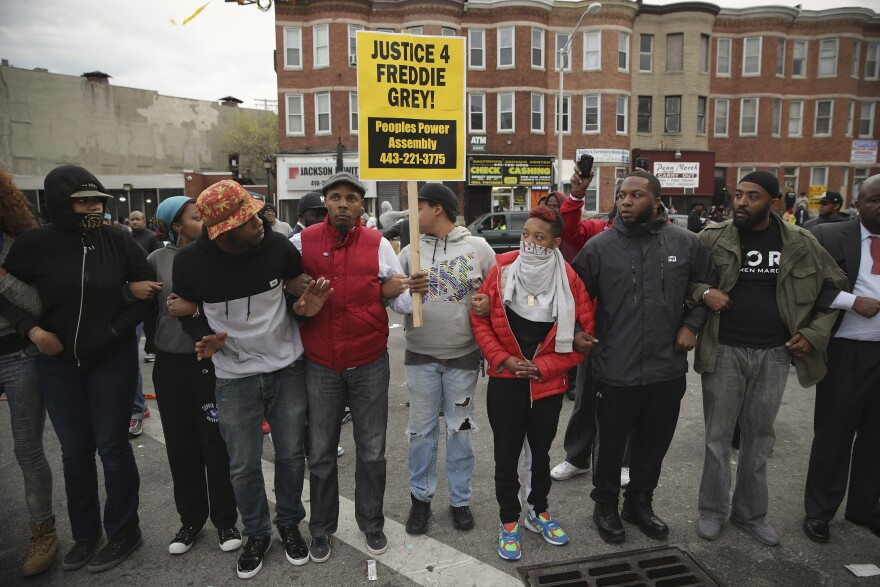 Baltimore residents lock arms and form a line opposing police during protests at the corner of Pennsylvania and North avenues following the funeral of Freddie Gray.