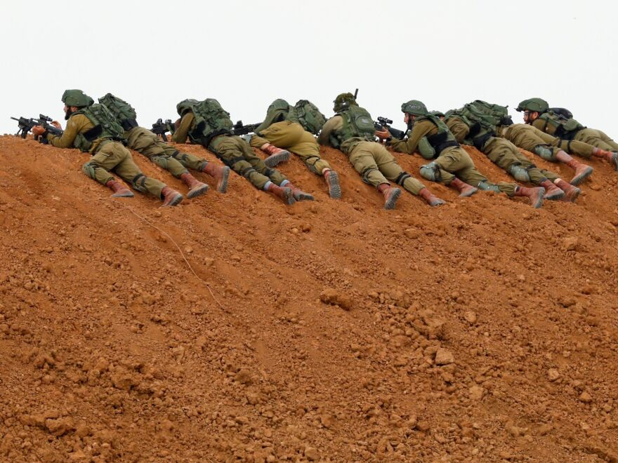 With tensions high and clashes possible, Israeli soldiers keep watch from atop an earth barrier along the border with Gaza on Friday.