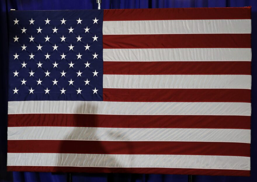 President Trump's shadow is shown on an American flag. (Chuck Burton/AP)