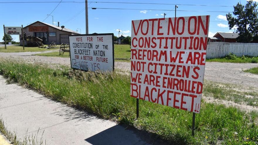 Signs in Browning urge tribal members to vote for and against the proposed reform to the constitution.