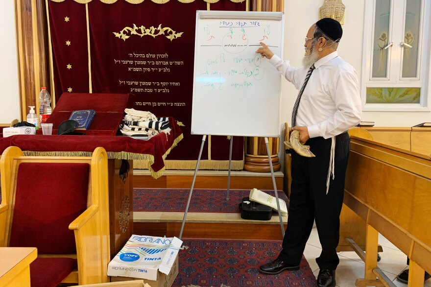 Rabbi Yehonatan Adouar teaches a shofar blowing course in Rambam Synagogue. He is indicating how to take breaths during the traditional rhythms of the shofar during prayers.