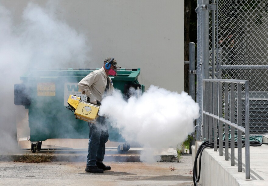 A Miami-Dade County mosquito control worker sprays around a school in the Wynwood area of Miami earlier this month.