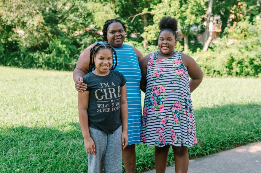 Tranese (left), Harriet and Talayla Feggins stand outside their home in west Atlanta. Talayla, 13, relies on a machine to help with her asthma.