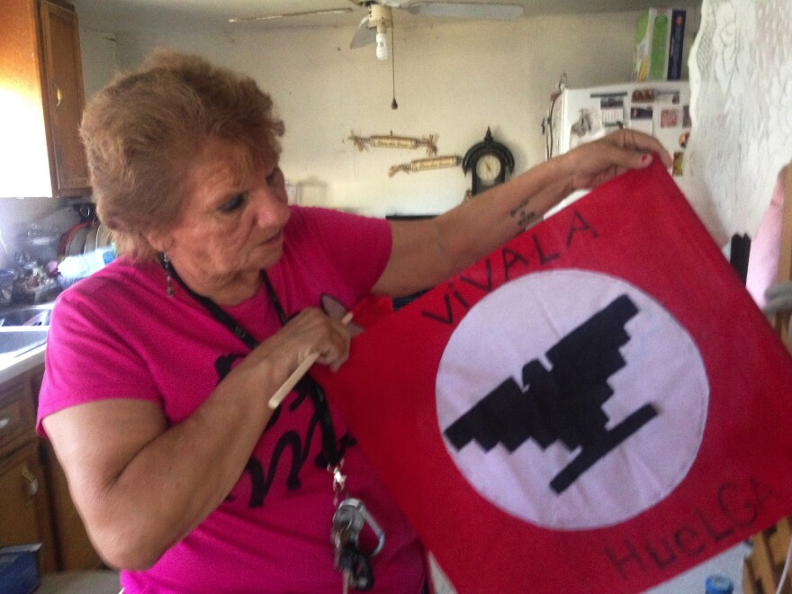 Daria Vera holds a banner from the 1966 farmworkers strike in Texas.