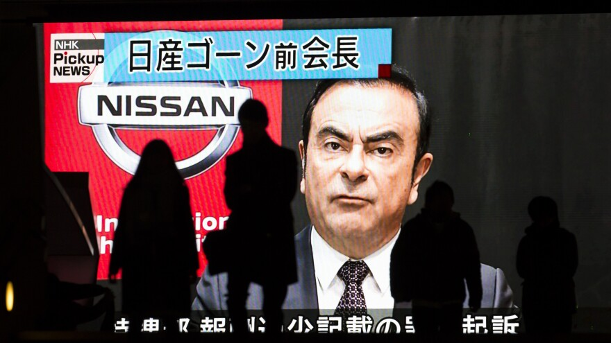Pedestrians walk in front of a monitor showing an image of former Nissan Motor Co. Chairman Carlos Ghosn on Monday in Tokyo, Japan. Ghosn, a veteran of the auto industry, was charged on Monday for financial misconduct after he was arrested in Tokyo last month on accusations he underreported his compensation to authorities.