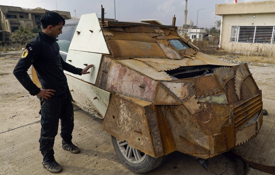 An Iraqi soldier on Sunday stands near a makeshift armored car left behind by the Islamic State when they were driven out of the eastern side of Mosul. President Trump has ordered the U.S. military to draw up a new plan for the fight against ISIS.