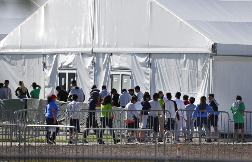 In this Feb. 19, 2019 file photo, children line up to enter a tent at the Homestead Temporary Shelter for Unaccompanied Children in Homestead, Florida.