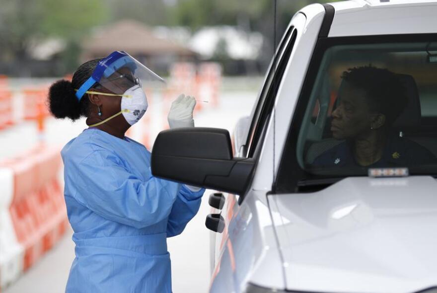Harris County Health Department nurse Harriet Lewis administers a coronavirus test at Stallworth Stadium