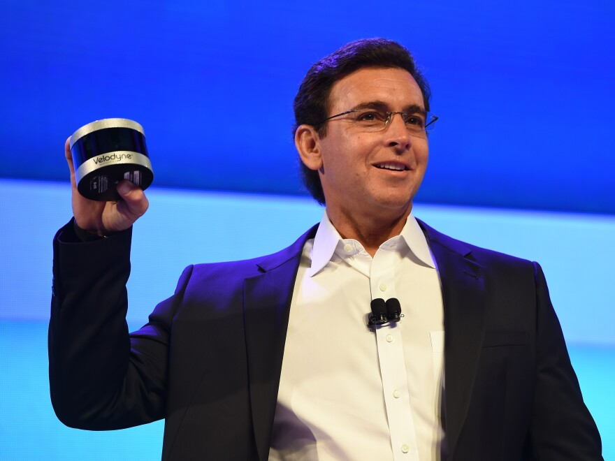 Ford CEO Mark Fields shows off the new Velodyne Puck sensor at a press conference Tuesday in Las Vegas, ahead of the CES 2016 Consumer Electronics Show. Veoldyne Lidar devices help autonomous cars scan the road ahead and plot a safe course.