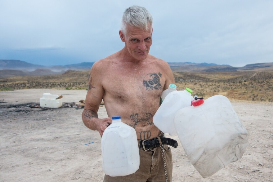Photo of a shirtless man standing under the desert sun, holding several empty plastic containers.