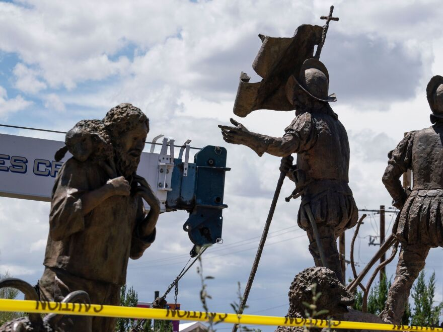 Workers for the city of Albuquerque, N.M., remove a sculpture of Spanish conquistador Juan de Oñate on Tuesday. A man was shot a day earlier as an armed militia group attempted to defend the statue from protesters.