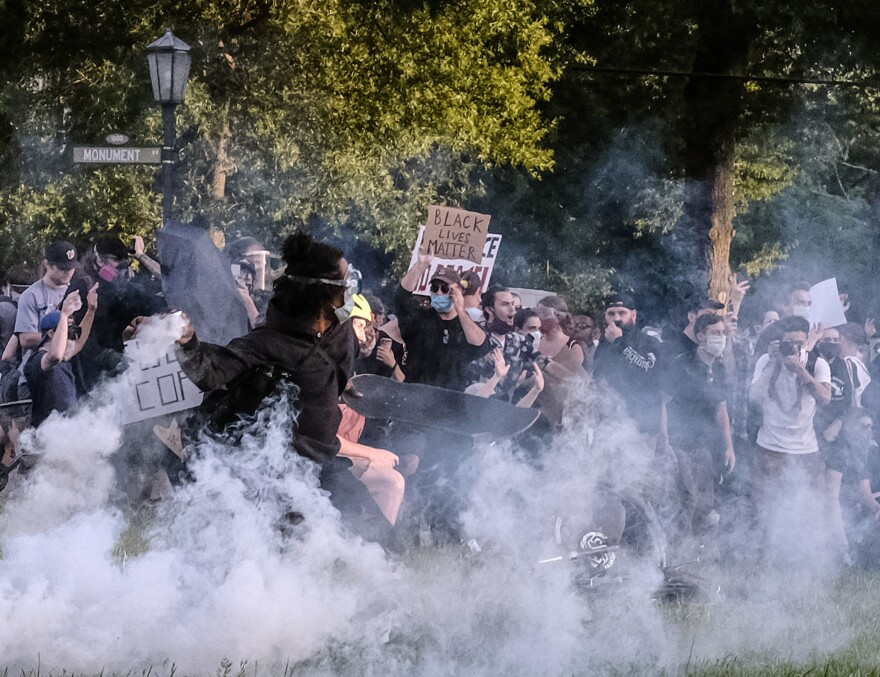 Protesters participating in a peaceful demonstration react to being hit by Richmond Police with tear gas and pepper spray on Monument Avenue at the Robert E. Lee statue on June 1, about 30 minutes before the city's curfew.