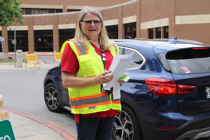 VA volunteer Barbara Abbey asks drivers questions about coronavirus symptoms, exposure, and recent travel history.