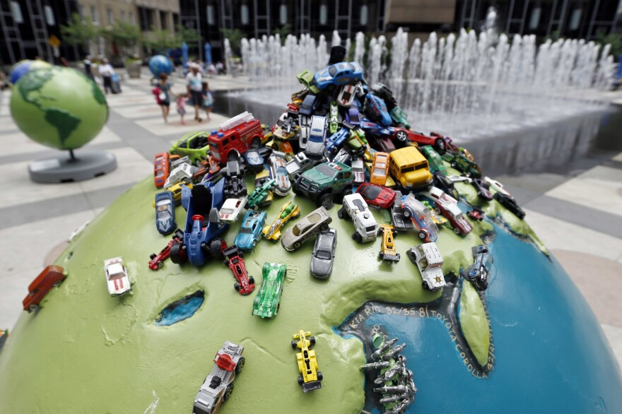 """People walk through public art, including one called """"Carpool"""", from the part of the Cool Globes exhibit surrounding the fountains in PPG Plaza on Thursday, June 21, 2018, in Pittsburgh. (Keith Srakocic/AP)"""
