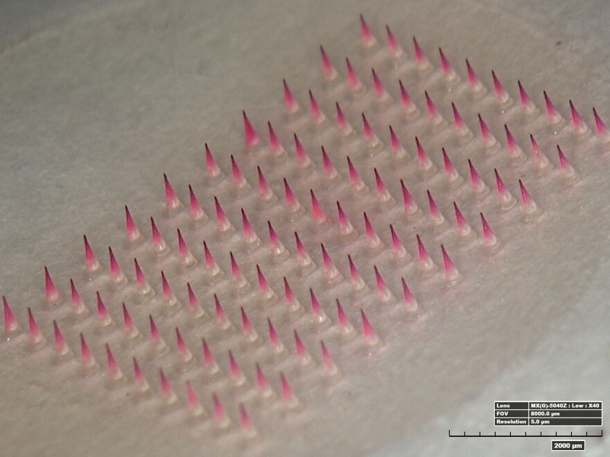 A magnified image shows a patch with its microneedles dyed pink.
