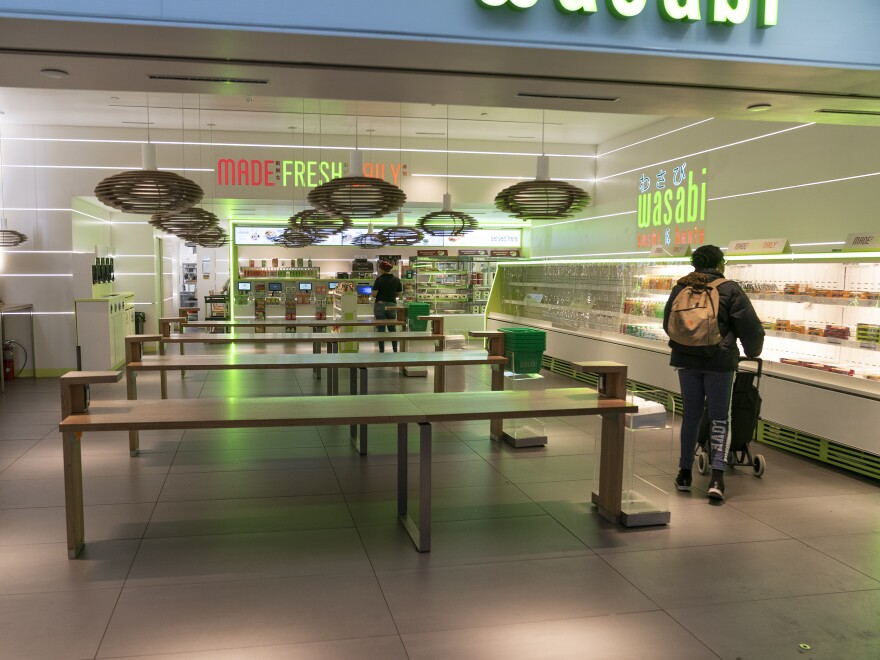 A shopper roams the Wasabi Store in Penn Station in New York on Monday. Food businesses are being urged to serve only take-out orders to reduce the spread of the novel coronavirus.