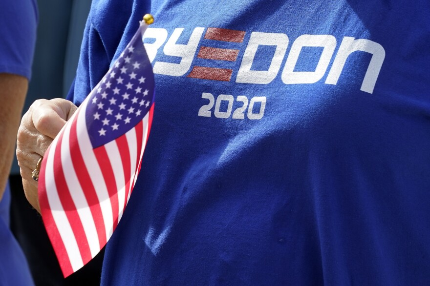 "A supporter wearing a ""Bye Don"" T-shirt waves a U.S. flag to support voters as they arrive at the Sumter County Elections office to drop their ballots off after taking part in a parade of over 300 golf carts supporting Democratic presidential candidate former Vice President Joe Biden Wednesday, Oct. 7, 2020, in The Villages, Fla."