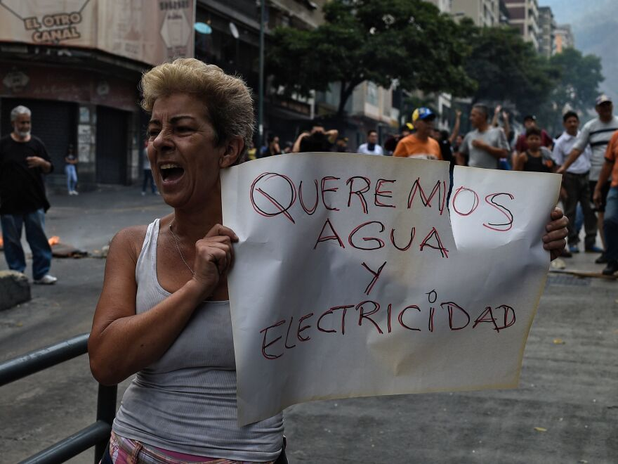 "A woman holds a placard reading ""We Want Water and Electricity"" as she shouts slogans during a protest in Caracas, Venezuela, about a lack of water and electric service during a new power outage in the country on Sunday. President Nicolás Maduro announced a 30-day electricity rationing plan to help as the government works to restore service."
