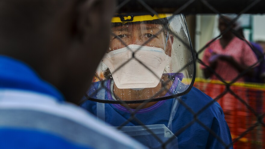 "Wencke Petersen, a Doctors Without Borders health worker, talks to a man through a chain link gate in September, when she was doing patient assessment at the front gate of an Ebola treatment unit. ""There were days we couldn't take any patients at all,"" she tells NPR."