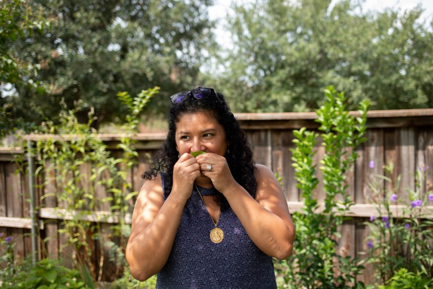 Xochitl Ortiz holds a leaf to her nose as she stands the family yard surrounded by a high wooden fence with plants growing against it.