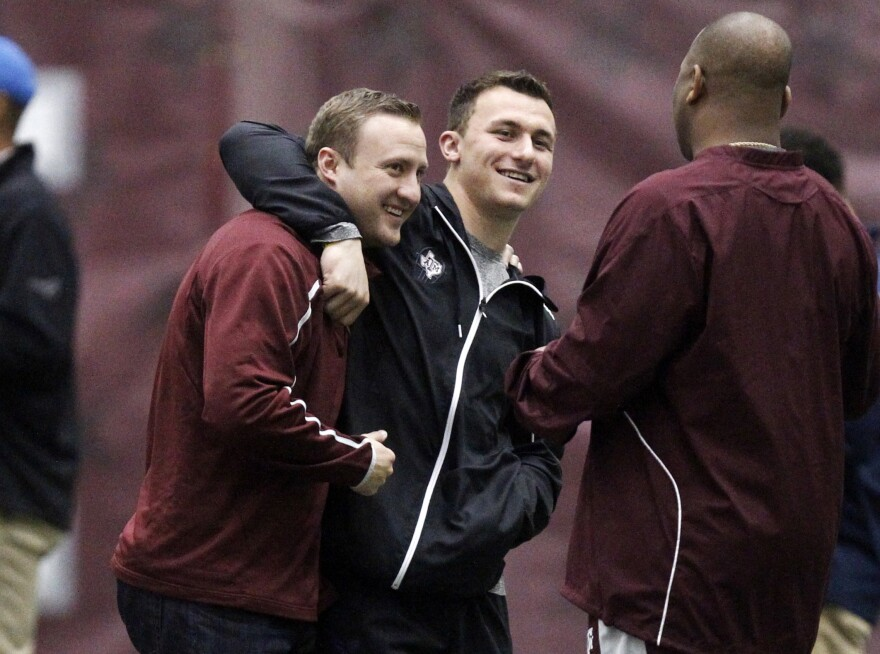 Former Texas A&M quarterback Johnny Manziel (middle) gives offensive coordinator Jake Spavital a hug during Texas A&M pro day on March 5, 2014, in College Station, Texas.