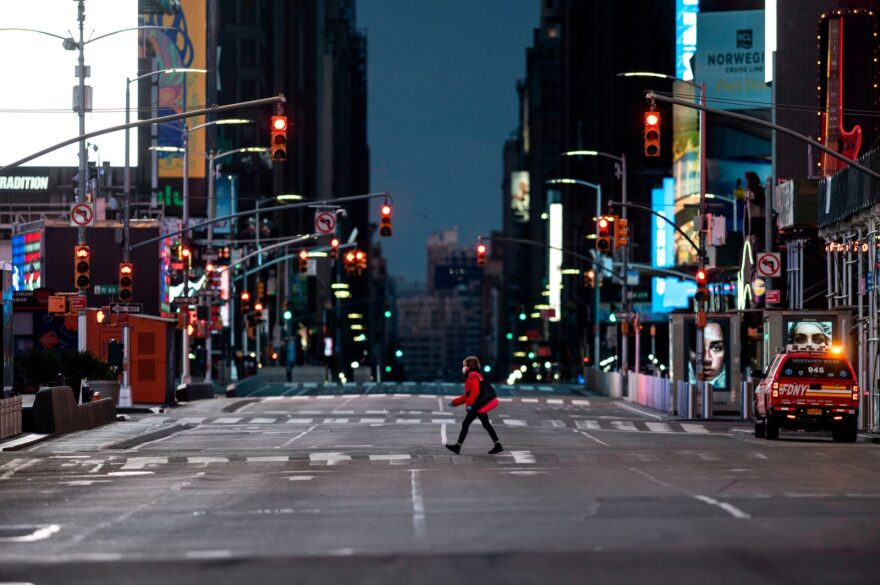 A woman walks through an almost-deserted Times Square in New York City.