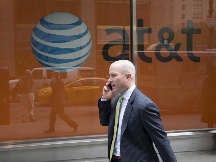 A man using a mobile phone walks past an AT&T store, in June. <em>The New York Times</em> and ProPublica report that the telecom giant helped the NSA spy for decades.