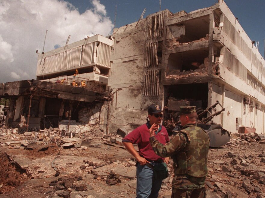 A U.S. Marine talks with an FBI investigator in front of the U.S. Embassy in the Tanzanian capital of Dar es Salaam after it was blown apart in a 1998 terrorist bombing.