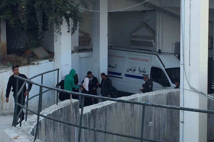 The family of a policeman killed during Wednesday's attack grieves outside the morgue in Tunis, Tunisia.