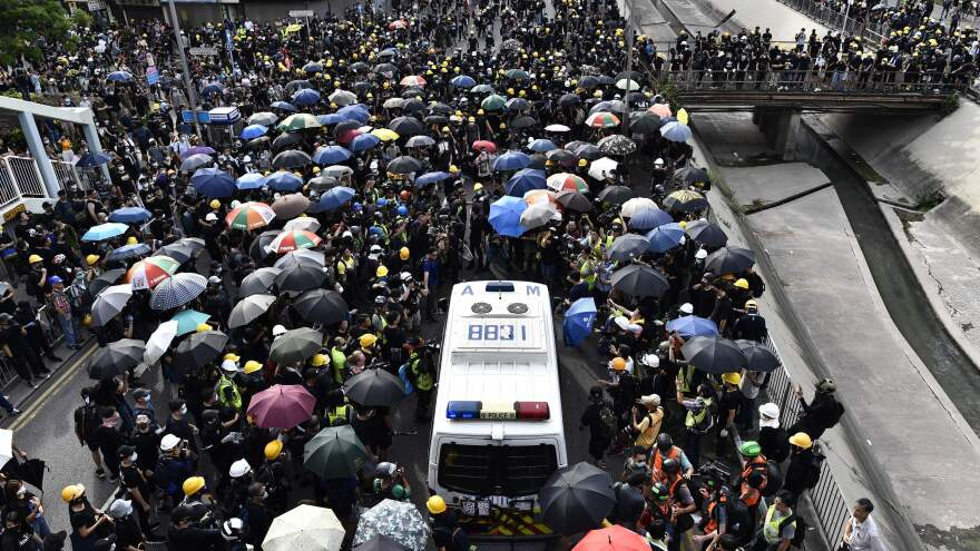 A crowd of protesters blocks a police van during a demonstration on Saturday.