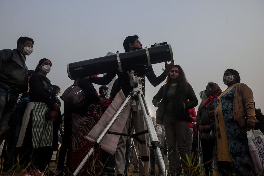 People stand in a queue to see the Great Conjunction of Jupiter and Saturn at the Maidan area in Kolkata, India.