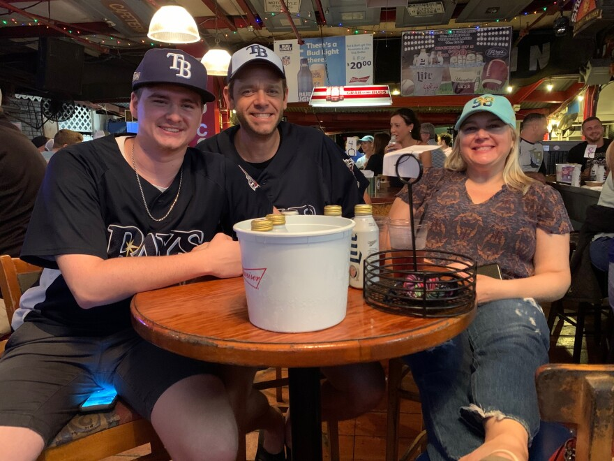 Parker Perry (left) sits at a table with his parents at Ferg's Sports Bar.