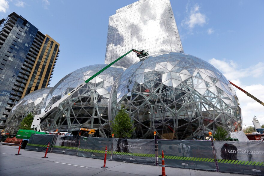 Amazon said Thursday that it will spend $5 billion to build another headquarters in North America to house 50,000 new employees. In April, workers constructed three glass-covered domes in an expansion of the company's downtown Seattle campus.