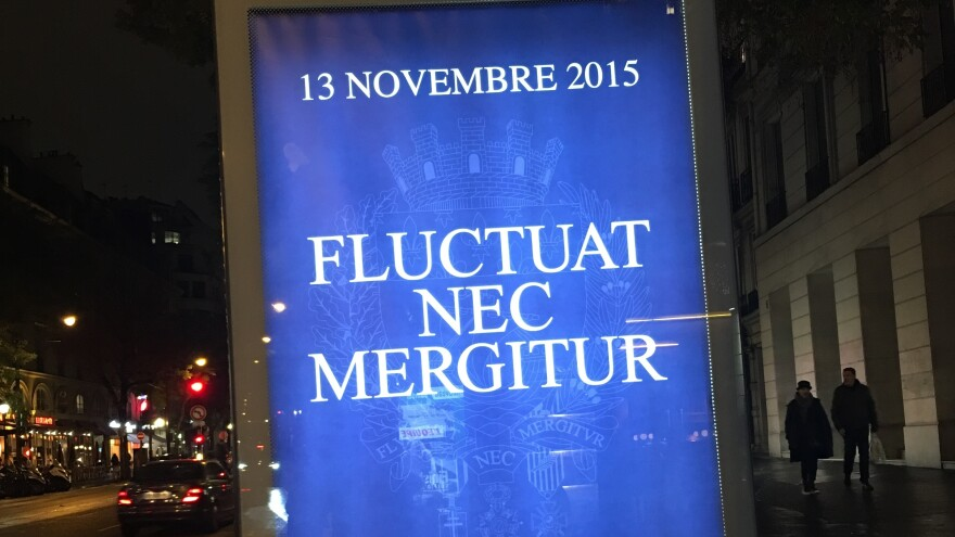 "A Paris billboard sports an oft-repeated motto in response to the terror attacks, ""<em>fluctuat nec mergitur,"" </em>or ""tossed but not sunk."""