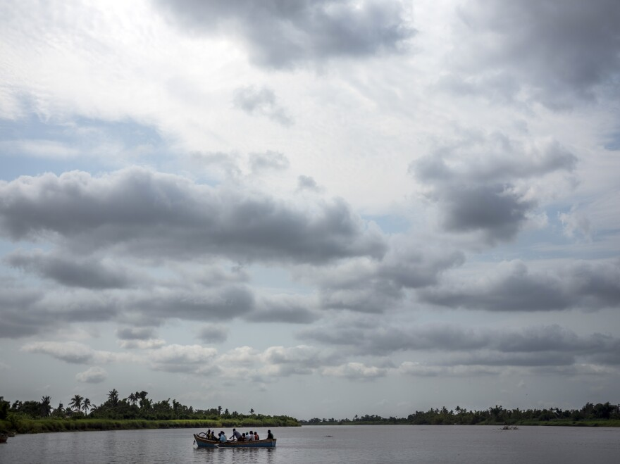 A boat ferries passengers across the river in Buzi district, Mozambique, on Nov. 14. Reliable weather radar data is not available in the region.