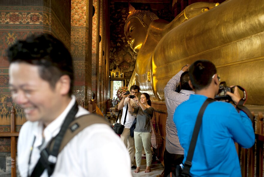 Tourists take pictures inside Wat Pho temple in Bangkok in August. Tourism, a key part of Thailand's economy, is down 20 percent this year following political violence and a military coup.