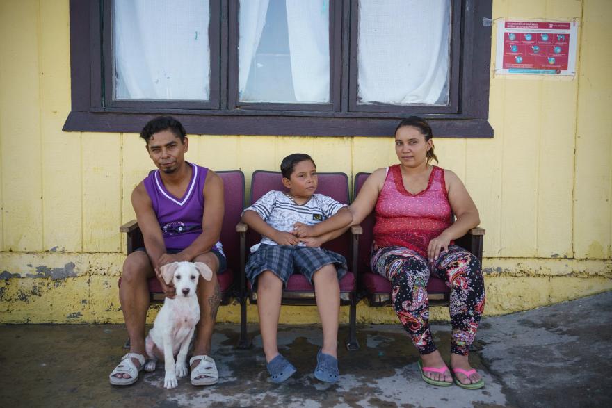 César, de 35 años, su esposa Carolina, de 25, y su hijo Donovan, de 9, frente a su casa compartida en el refugio para migrantes Pan de Vida, en Ciudad Juárez, México.