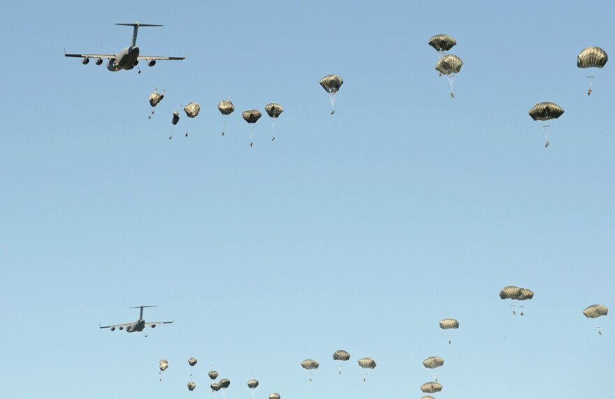 U.S. military planes drop paratroopers during a multi-national jump that includes soldiers from the U.S., Britain and Poland on June 7, near Torum, Poland. U.S. President-elect Donald Trump has questioned the value of the NATO alliances, raising worries among many European countries.
