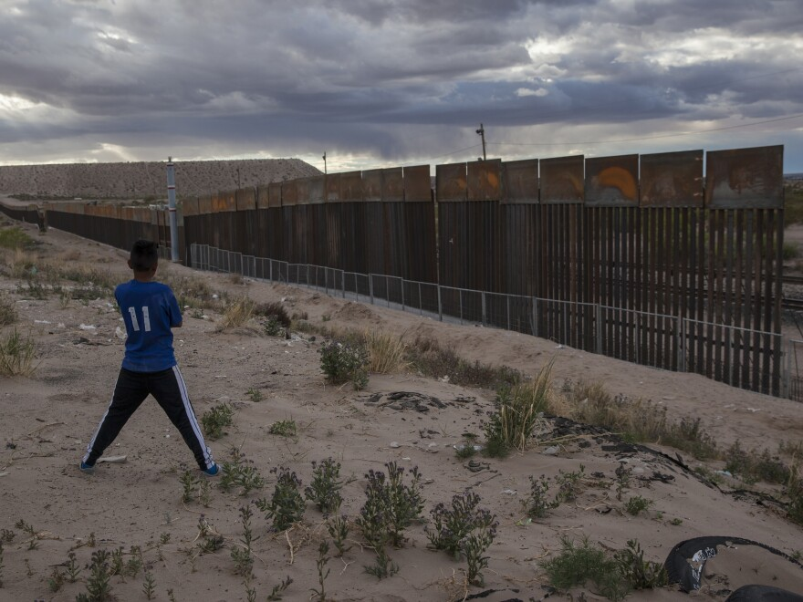 A youth looks at a new, taller fence being built along U.S.-Mexico border in Ciudad Juarez, Mexico, across the border from Sunland Park, N.M.