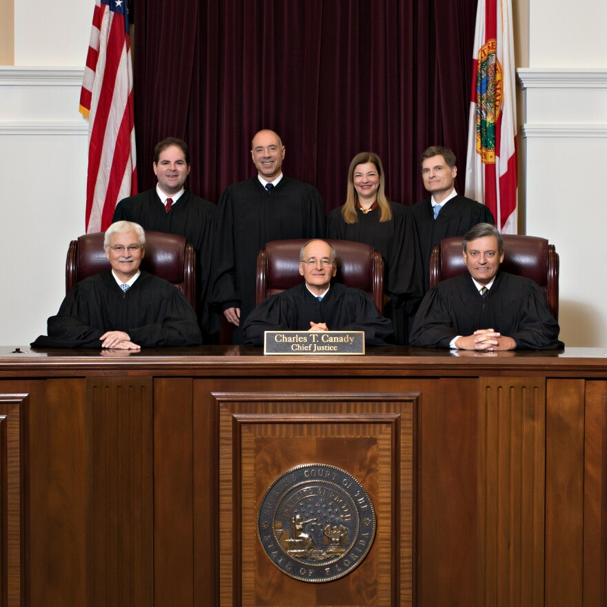 Three justices sit behind the bench. Behind them are four justices standing. Beside all seven justices is the American and Florida flags. Dark curtains are ruffled in the background.